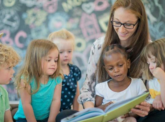 Leerkracht leest voor aan leerlingen